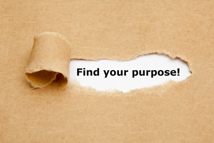"""""""Find your purpose"""" appearing behind torn brown paper."""