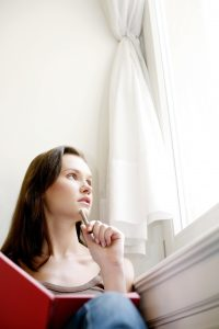 woman thinking and reflecting looking out a window