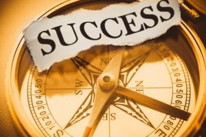 Word success overlaying the image of a magnetic compass